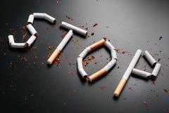 СТОП надписи от сигарет на черной предпосылке Остановите курить Концепция куря убийств Надпись мотивации к стоковое изображение