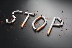 СТОП надписи от сигарет на черной предпосылке Остановите курить Концепция куря убийств Надпись мотивации к стоковое фото