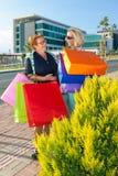 Стоп 2 счастливый женщин вне ходя по магазинам, который нужно побеседовать Стоковая Фотография