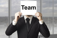 Сторона бизнесмена пряча за командой знака Стоковые Изображения