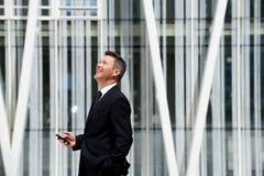 Сторона бизнесмена смеясь над и держа мобильным телефоном стоковые изображения