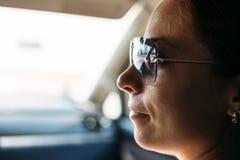 Сторона девушки в стеклах солнца внутри автомобиля стоковые изображения
