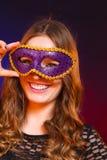 Сторона женщины крупного плана с маской масленицы фиолетовой на темноте Стоковое Изображение