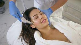 Сторона заботы кожи, женщина клиента на процедурах по косметики rejuvenating с технологией поставки активного компонента в красот акции видеоматериалы