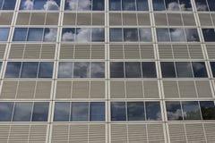 Сторона здания небоскреба с серыми панелями и окна которая отражают небо с облаками i Стоковые Фото