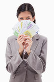 Сторона коммерсантки пряча за деньгами Стоковая Фотография