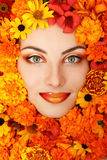 Сторона красоты женщины с оранжевыми цветками стоковые изображения rf