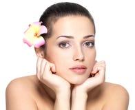 Сторона красоты молодой женщины с цветком. Концепция косметики Стоковое фото RF