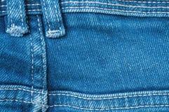 Сторона крупного плана поверхностная задняя старой голубой ткани брюк демикотона текстурировала предпосылку Стоковые Фотографии RF