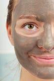 Сторона крупного плана женская с маской ухода за лицом грязи глины Стоковое Изображение RF