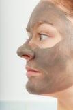 Сторона крупного плана женская с маской ухода за лицом грязи глины Стоковое фото RF
