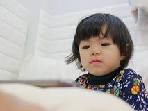 Сторона маленького ребенка, 2 лет старого, пока наблюдать/вытаращить на смартфоне стоковые фотографии rf