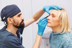 Сторона маркировки пожилой женщины старая пластической хирургии на receptio Стоковое Изображение