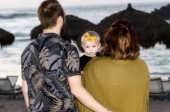 Сторона матери & отца далеко от камеры при младенец смотря камеру при младенец наблюдая Солнце установленное в Мексику Стоковое Изображение