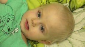 Сторона маленькой прелестной девушки пряча под одеялом 4K UltraHD, UHD видеоматериал