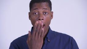 Сторона молодого африканского бизнесмена смотря сотрясенный и покрывая рот акции видеоматериалы