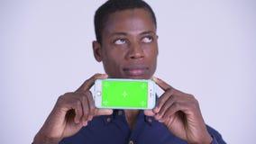 Сторона молодого счастливого африканского бизнесмена думая пока показывающ телефон сток-видео