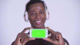 Сторона молодого счастливого африканского человека думая пока показывающ телефон готовый на зима сток-видео
