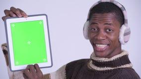 Сторона молодого счастливого африканского человека показывая цифровой планшет и смотря удивила готовое на зима сток-видео