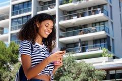 Сторона молодой женщины идя с сотовым телефоном снаружи Стоковое Фото