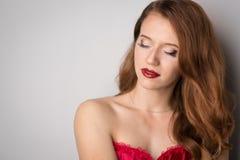 Сторона молодой красивой женщины брюнет на темной предпосылке в красном цвете стоковые изображения rf