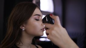 Сторона молодой милой девушки во время процесса макияжа с распыляет Художник красивого брюнета женский делает идеальный видеоматериал