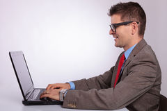 Сторона молодого бизнесмена работая на компьтер-книжке стоковая фотография