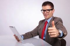 Сторона молодого бизнесмена с таблеткой, показывая большой палец руки вверх Стоковые Изображения