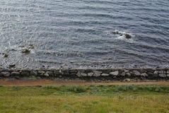 Сторона пляжа с большими камнями и зеленой травой стоковое изображение rf