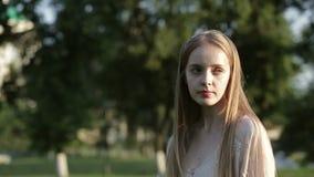 Сторона портрета бутылки с водой питья молодой женщины на парке зеленого цвета лета сток-видео