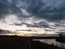 Сторона сельской местности ночного неба драматического солнца установленная реки Стоковое Фото
