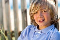 Сторона снятая красивого мальчика рядом с загородкой. Стоковое Изображение