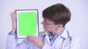 Сторона счастливого молодого красивого доктора человека показывая цифровой планшет видеоматериал