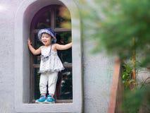 Сторона счастливой маленькой девочки усмехаясь на предпосылке bokeh с годом сбора винограда стоковые фотографии rf