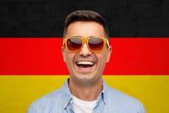 Сторона усмехаясь человека в солнечных очках над немецким флагом стоковые фотографии rf