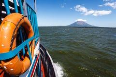 Сторона цветастого ferryboat при померанцовое кольцо спасательного жилета быстро проходя вперед в озере к вулкану Стоковая Фотография RF