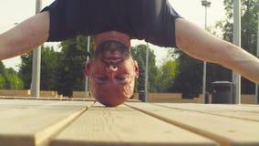 Сторона человека делая headstand в парке