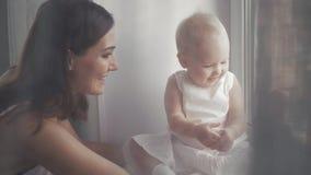 Стороны счастливой семьи смеясь над, мать держа прелестный ребёнок ребенка, усмехаясь и обнимая, близкая поднимающая вверх границ Стоковое Изображение RF
