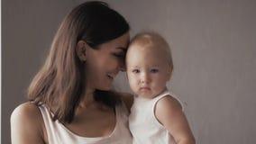 Стороны счастливой семьи смеясь над, мать держа прелестный ребёнок ребенка, усмехаясь и обнимая, близкая поднимающая вверх границ Стоковые Изображения