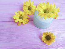 Стоцвет Cream продукта опарника косметического желтый цветет розовая деревянная предпосылка Стоковое Изображение
