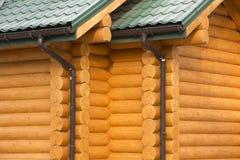 Сточная канава на деревянном доме с крышей зеленого битумного толя стоковые фото