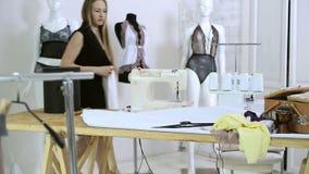 Сточная труба женщины приходит положить на полку с вешалками для того чтобы выбрать сексуальное нижнее белье сток-видео
