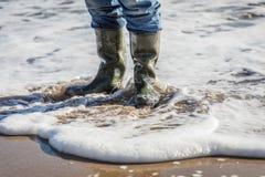 Стоять в воде на пляже с wellies Стоковая Фотография RF