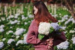 Стоять женщины поворачивает вокруг к цветкам гортензии сада стоковые фото
