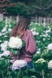 Стоять женщины поворачивает вокруг к цветкам гортензии сада стоковая фотография
