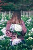 Стоять женщины поворачивает вокруг к цветкам гортензии сада стоковое фото rf