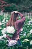 Стоять женщины поворачивает вокруг к цветкам гортензии сада стоковая фотография rf