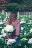 Стоять женщины поворачивает вокруг к цветкам гортензии сада стоковое фото