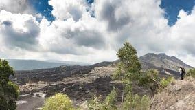 Стоять туристский на холме и выглядит черными утесами лавы и драматическим облачным небом Панорамный вид наклонов вулкана Batur стоковые изображения