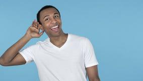 Стоящая африканского человека слушая секретная, голубая предпосылка